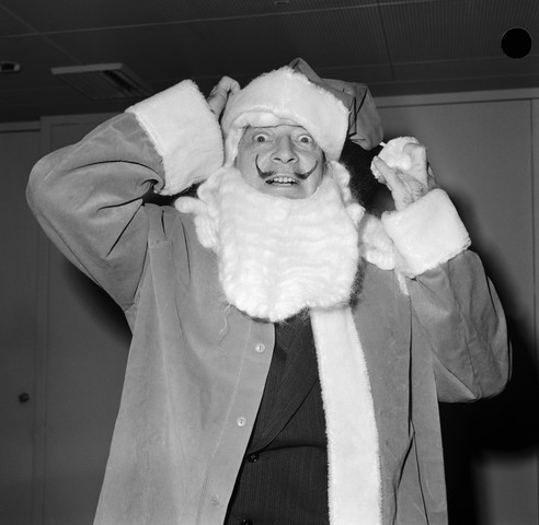 """12/22/1961-Salvador Dali, Spanish painter, wearing Santa claus beard and a hat of his own creation called """"Dali's Complex."""" Photograph. --- Image by © Bettmann/CORBIS"""